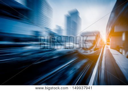 cityscape with road traffic and speeding train,suzhou,blue toned,china,asia.