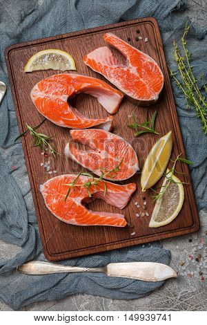 Steak of fresh salmon with lemon, aromatic herbs and spices on cutting board. Top view with copy space.