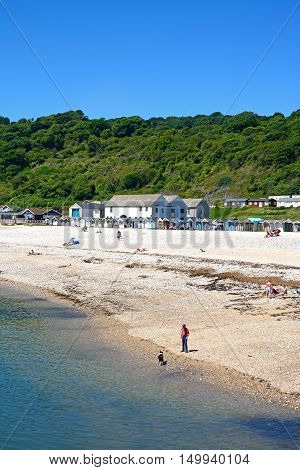 LYME REGIS, UNITED KINGDOM - JULY 18, 2016 - Holidaymakers relaxing on the beach with beach huts and town buildings to the rear Lyme Regis Dorset England UK Western Europe, July 18, 2016.