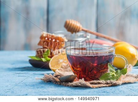 Cup of ginger tea with honey and lemon on blue background