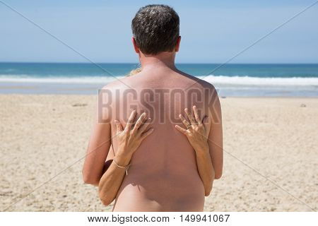 Naked Couple Standing On The Beach Back View
