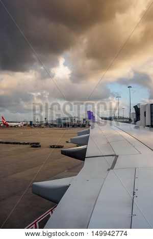 Sydney, Australia - Dec 23, 2015: Onboard Hawaiian Airlines. Plane landed in Sydney International Airport in late afternoon sun and storm clouds. The plane is now stationary and docked to the jetway.