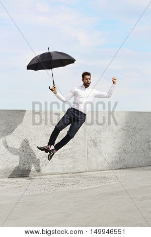 Cool buisness Man with umbrella jumping for joy