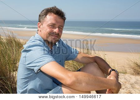Handsome Man Relaxing On The Beach, Sitting On The Sand