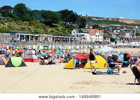 LYME REGIS, UNITED KINGDOM - JULY 18, 2016 - Holidaymakers relaxing on the sandy beach with the promenade and beach huts to the rearr Lyme Regis Dorset England UK Western Europe, July 18, 2016.