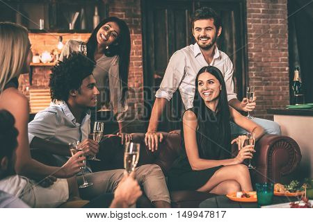 Friends gathering. Group of cheerful young people enjoying food and drinks while spending nice time in cofortable chairs at home together