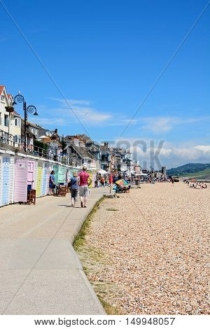LYME REGIS, UNITED KINGDOM - JULY 18, 2016 - View of the pebbly beach with the promenade and beach huts to the left hand side Lyme Regis Dorset England UK Western Europe, July 18, 2016.