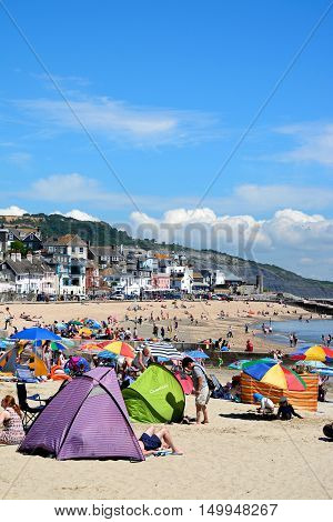 LYME REGIS, UNITED KINGDOM - JULY 18, 2016 - Holidaymakers relaxing on the beach with town buildings to the rear Lyme Regis Dorset England UK Western Europe, July 18, 2016.