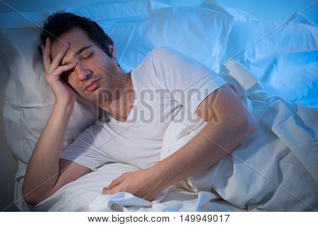 Worried man lying in bed in the morning