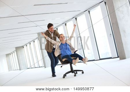 Full length of young businessman pushing female colleague in chair at empty office