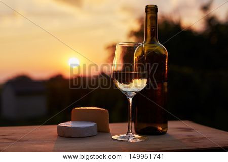 Low Key Image, Glass Of White Wine With Bottle And Cheese On Wooden Table, Toned At Sunset.