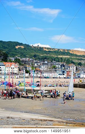 LYME REGIS, UNITED KINGDOM - JULY 18, 2016 - Group of people with dinghies at the harbour entrance with the beach and town to the rear Lyme Regis Dorset England UK Western Europe, July 18, 2016.