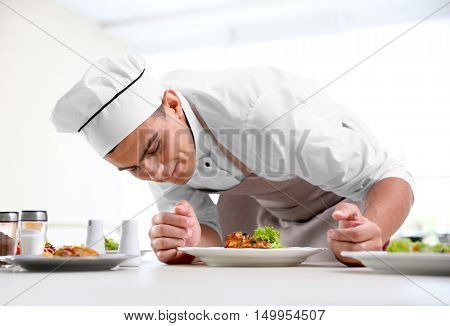 Young chef cook decorating meat dish in kitchen