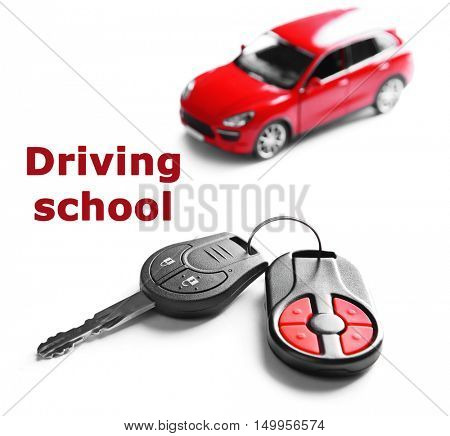 Driving school concept. New red car with keys, isolated on white