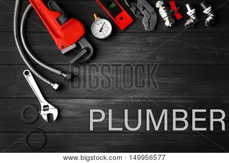 Plumbing concept. Plumber tools on a gray wooden background