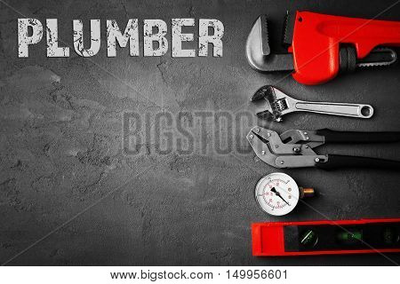 Plumbing concept. Plumber tools on concrete structure background