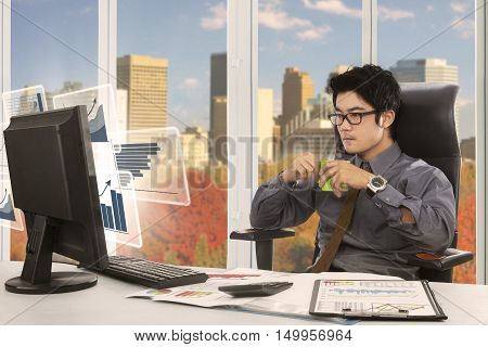 Picture of Asian entrepreneur sitting in the office while drinking a cup of coffee and looking at virtual financial chart on the computer