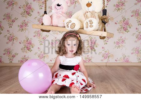 little girl in a beautiful dress near a swing in studio there are two teddy bear sitting on the swing. girl holding a pink balloon