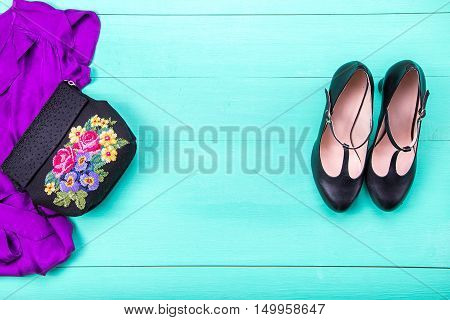 women's clothes - dress embroidered bag black heels earrings nail polish lipstick. turquoise wooden background top view