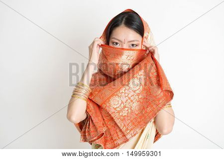 Portrait of secrecy mixed race Indian Chinese woman in traditional sari dress, covering face and looking at camera, on plain background.