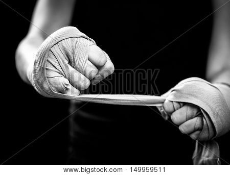 Woman is wrapping hands with pink boxing wraps. Isolated on black with red nails. Strong hand and fist ready for fight and active exercise