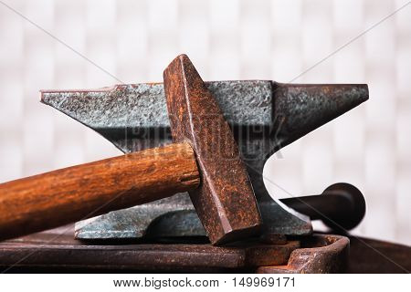 Old rusty rugged anvil with hammer on white checkered background.
