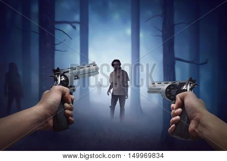 Man hand holding two gun and ready to shooting walking zombie to him
