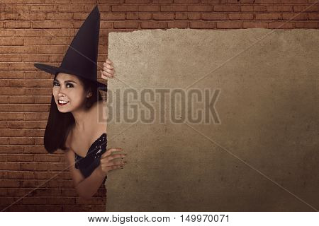 Beautiful Asian Woman With Hat And Witch Costume Hiding And Peek Form Behind Blank Parchment