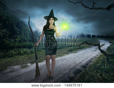 Charming Halloween Asian Witch With Magic Light Holding Broom