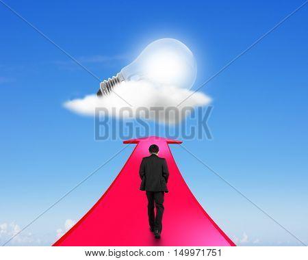 Businessman Walking On Arrow Going Upward Toward Light Bulb