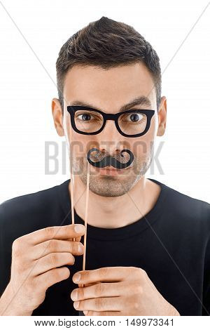 Young Handsome Man With Paper Moustaches And Glasses Making Faces
