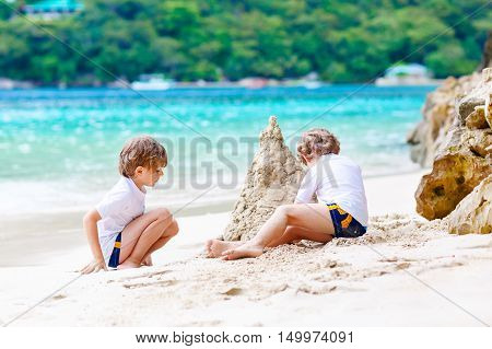 Two little kids boys having fun with building a sand castle on tropical beach of Haiti. children playing together on their vacations.