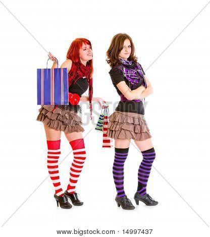 Happy young girl with shopping bags standing behind her dissatisfied girlfriend isolated on white