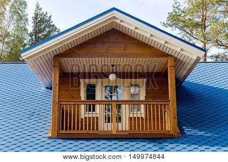 wooden balcony in a small house with a blue roof polycarbonate autumn day
