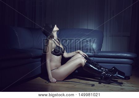 Sensual woman in underwear and lace eye cover and latex boots sit on floor in dark desire