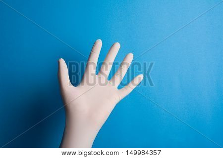 Horizontal front view of hand with surgical white glove on blue background