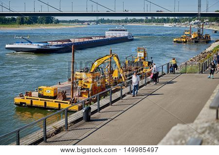 DUESSELDORF, GERMANY - AUGUST 17, 2016: A dredger works at the quay of river Rhine along the Rhine promenade