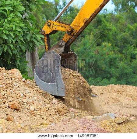 excavation power bucket scooping up dirt from a pile, construction site near Songkhla, Thailand