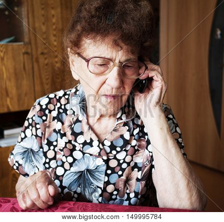 Old woman talking on mobile phone. Elderly, mature female at home
