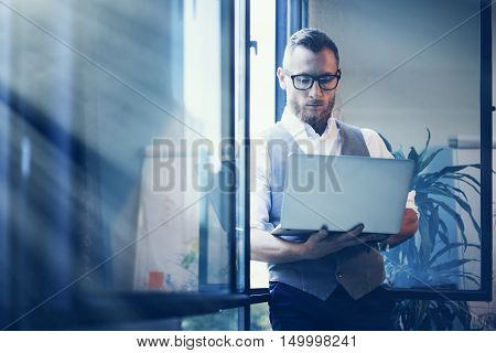 Young Bearded Businessman Wearing Glasses White Shirt Waistcoat Working Modern Laptop Holding Hands Near Panoramic Window.Man Work Office Startup Project.Sunlight Effect.Blurred Background
