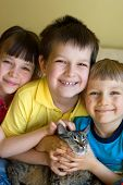 A sister and two brothers are smiling as they are hugging their pet cat. poster