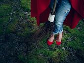 Witch legs in red shoes standing in the woods with a broom in his hand.Halloween holiday. poster