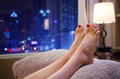 Woman puts her feet with red pedicure on pillow near window with city view poster