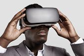 3d technology virtual reality entertainment cyberspace concept. Young dark-skinned entrepreneur wearing formal suit using oculus rift headset with head-mounted display playing video game in office poster