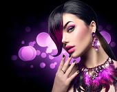Sexy Beautiful fashion woman with purple dyed hair fringe hairstyle and violet color accessories, necklace and earrings with crystals. Beauty model girl portrait isolated on black background. poster