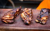 Grilled spare beef or pork back ribs prepared in smoker. Delicious roasted cuts of meet made on barbecue smoker on a wooden cutting desk. poster