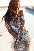 Beautiful girl wearing bohemian chic clothing with flash tattoo on her body posing on the shore in sunlight poster