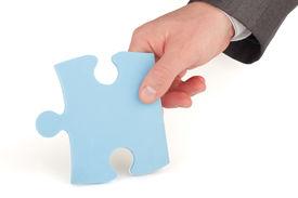 Businessman holding a piece of blue puzzle