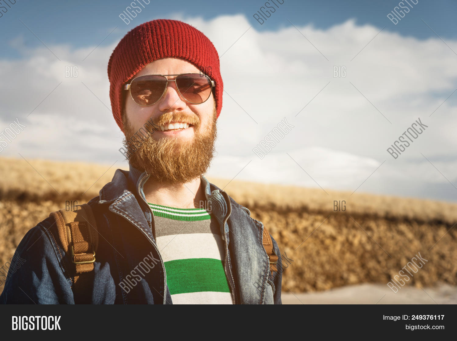 Portrait Of A Young Hipster Man Wearing Sunglasses And A Hat. A Smiling Bearded  Man 2f43f824bd84
