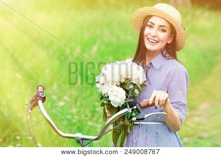 Pretty woman biker with bunch of peony is smiling to you